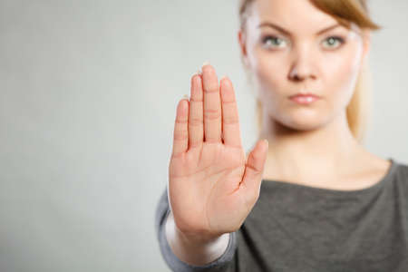 Communication psychology negative defensive concept. Assertive woman making stop gesture. Strong blonde lady showing hold sign. Stock Photo