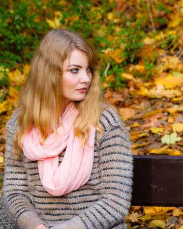 Season, relaxation and people concept. Young thoughtful blonde woman sitting on bench in autumnal park on sunny day Stock Photo