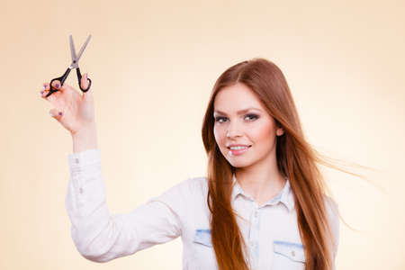 haircare: Haircare concept. Cutting and trimming. Young prefessional female barber hairstylist with scissors. Portrait of long haired girl prepared to styling hair.