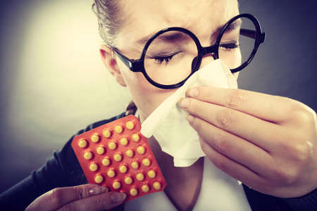 grippe: Sickness and diseases at work. Young unhealthy businesswoman with tissue having flu grippe. Secretary accountant with illness and pills spreads disease.