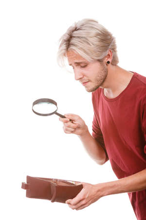 lack: Broke young man holding magnifying glass looking for banknotes in empty wallet purse. Lack of money. Crisis and weak economy concept, isolated on white