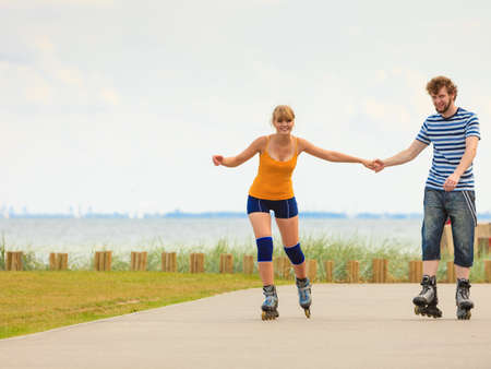 roller blade: Holidays, active people and friendship concept. Young fit couple on roller skates riding outdoors on sea shore, woman and man rollerblading together on the promenade Stock Photo