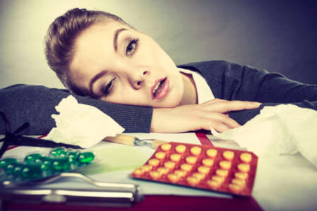 sleeping pills: Health concept at business work. Tired overworked young businesswoman secretary manager. Sick ill young female sleeping at workplace. Stock Photo