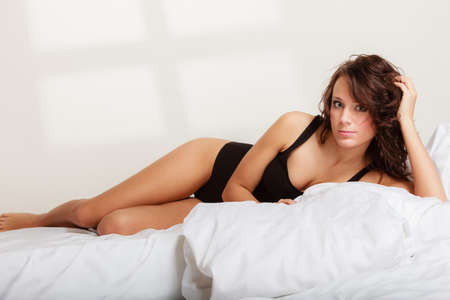 Sexy lazy girl in black body underwear lying on the bed. Young woman relaxing lazing in her bedroom at the morning.
