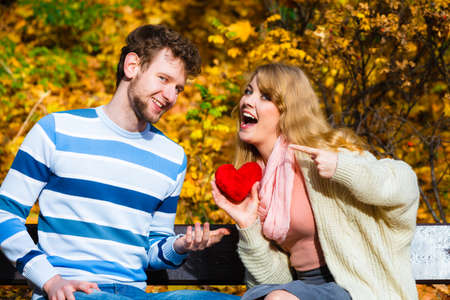 confessing: Accepting and sharing feelings. Confessing love and affection with romantic gesture. Positive reaction. Pair sit on bench in park woman present plush heart toy to man. Stock Photo