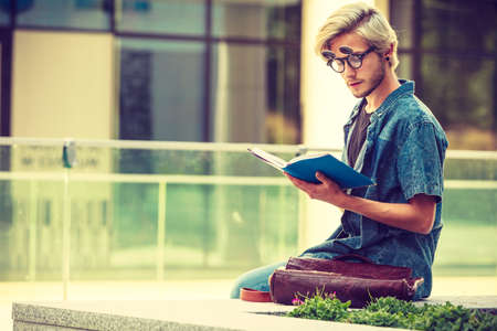 Male fashion, student concept. Guy holding and studying from notebook wearing jeans outfit and eccentric sunglasses sitting on white ledge next to modern building