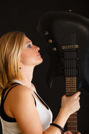musically: Music, singing concept. Blonde musically talented woman holding electric guitar with eyes closed on black background