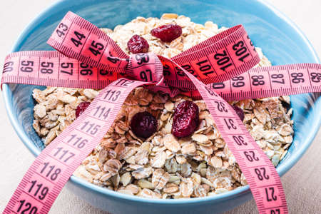 Diet healthy food weight loss concept. Oatmeal in blue bowl with measuring tape around on kitchen table Stock Photo