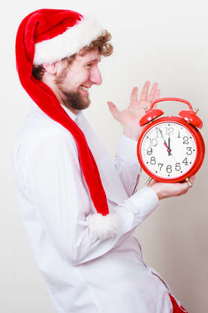 xmass: Happy man in santa claus hat holding alarm clock on gray. Christmas time season concept.