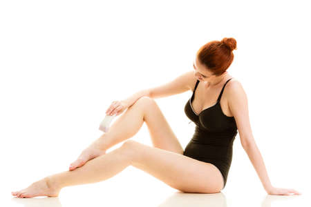 woman foot: Depilation, epilation, hygiene concept. Redhead woman shaving her legs with electric shaver depilator wearing black swimsuit, isolated.