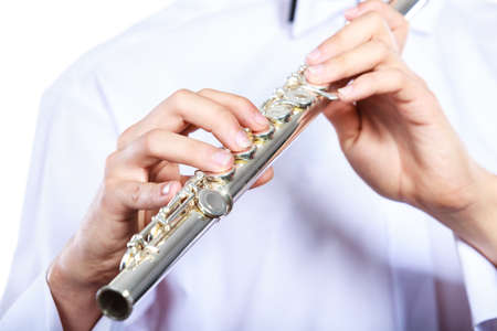 concert flute: Hands of young man playing the flute. Male flutist musician performer holding instrument, close up