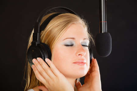 musically: Music, passion, stage-fright concept. Blonde young woman singing to microphone and wearing big headphones on her head performing songs in studio. Stock Photo