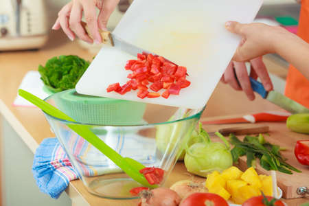 throwing knife: Healthy eating, vegetarian food, cooking, dieting and people concept. Woman in kitchen at home preparing fresh salad slicing vegetables throwing red pepper into bowl Stock Photo