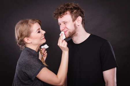 hygienic: Hygiene and skincare concept. Protection and help in relationship. Smiling happy woman wipe cream face nose of funny man by hygienic tissue. Girlfriend takes care of her boyfriend. Stock Photo