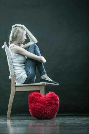 Broken heart love concept. Sad unhappy woman sitting on chair red heart pillow on floor dark background Stock Photo