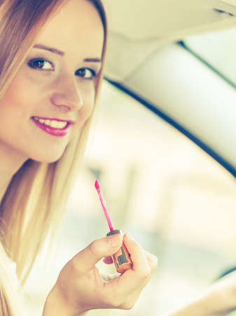 reckless: Distracted driver. Young attractive woman painting her lips doing applying make up while driving the car.