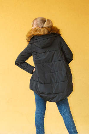 warm jacket: Attractive fashionable girl wearing black warm jacket on orange brown wall background. Fashion in winter time. Back view