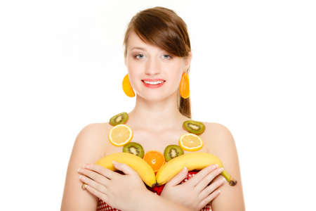 recommending: Diet. Girl with necklace and earrings of fresh citrus fruits holding bananas isolated. Woman recommending healthy nutrition Stock Photo