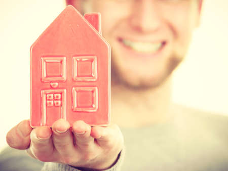 ownerships: Symbolism housing safety family finances mortgage concept. Young man holding house on palm. Male presenting home model.