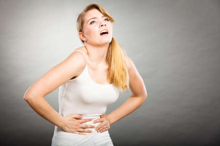 Health care concept. Bellyache, indigestion or menstruation. Young female suffering from strong stomach ache abdominal pain on gray