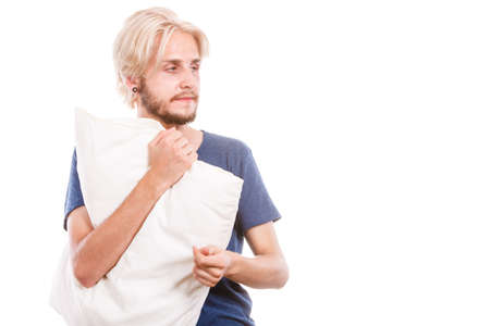 slumber: Health balance sleep deprivation concept. Sleepy tired guy holding pillow almost falling asleep. Health balance sleep deprivation concept. Male student or worker with lack of slumber, isolated on white