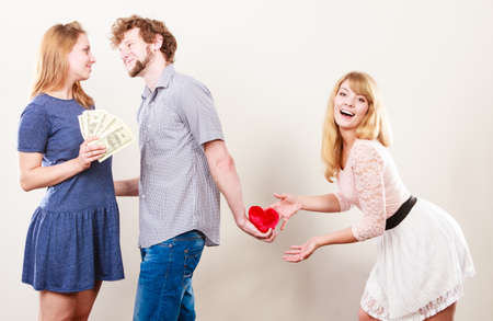 mislead: Cheating and cunning idea. Handsome sneaky man tricking rich woman for his true love. Triangle concept. Stock Photo