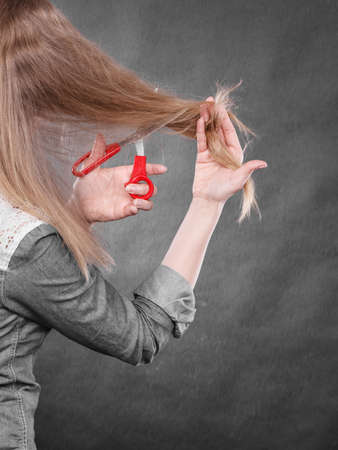 new look: Cutting coiffure and new look. Part body blonde woman cut her long straight hair. Female hands with red scissors making modern hairstyle. Stock Photo