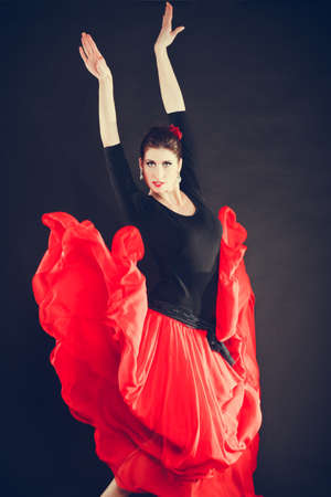 talented: Culture in move. Beautiful talented girl making performance by oriental dance. Woman in action dancing in long flared red skirt on black background. Stock Photo