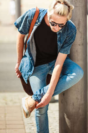 metrosexual: Men fashion, urban style clothing concept. Hipster guy walking through city wearing jeans outfit, male handbag and sunglasses on sunny day