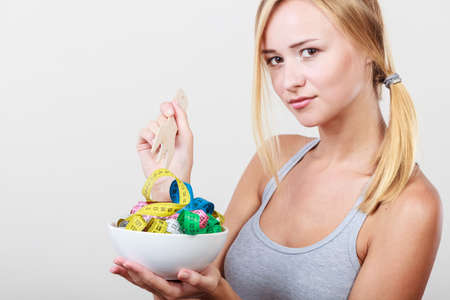 Diet, healthy eating, weight loss and slim body concept. Fit fitness girl holding bowl with many colorful measuring tapes Stock Photo