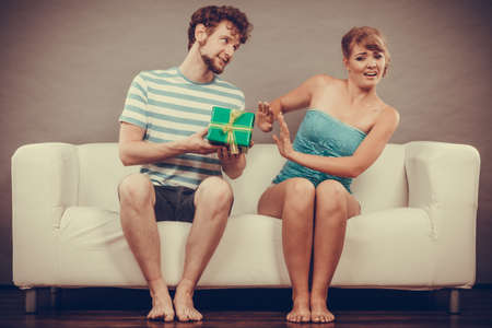 offended: Couple sitting on couch at home. Young man giving offended woman gift box, girl refusing to accept present Stock Photo