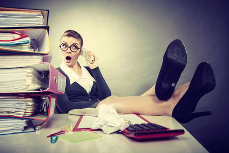 lovely businesswoman: Responsibilities at work concept. Young elegant relaxed woman secretary making phone call. Lovely businesswoman using traditional telephone.