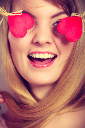 blinded: Love and happiness concept. Cheerful enjoyable young female with little small hearts on sticks covering woman eyes. Lovers blinded by their big love. Stock Photo