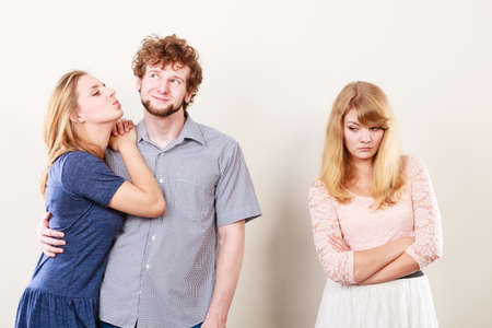 celos: Los celos y el concepto de traición. Muchacha abandonada jelous viendo en la feliz pareja abrazos. relación de triángulo.