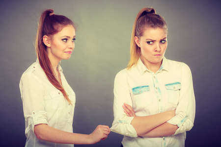 Young woman asking apologize to her offended friend after quarrel. Interpersonal conflict, bad relationships, friendship difficulties concept. Stock Photo