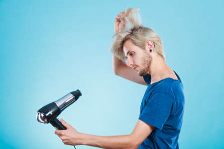 in vain: Style and fashion. Young trendy male hairstylist barber with new idea of look changing. Blonde man holding hair dryer and comb creating new hairdo, on blue