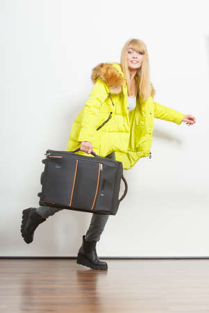 Young woman in warm jacket with suitcase running late. Gorgeous blonde tourist travel girl. Tourism.