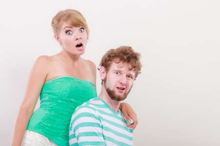 silly face: Funny playful young couple making silly face blonde girl and bearded guy studio shot