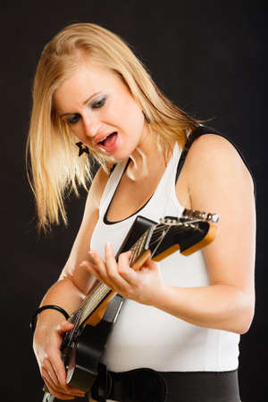 musically: Music, singing concept. Musically talented woman playing on electric guitar and singing, black background