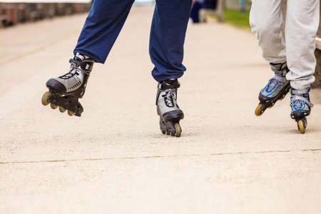 Spending free time together in summer. Hobby and lifestyle. Exercising and healthy body. Close up of legs in sportswear riding rollerskates.