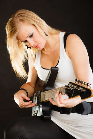 musically: Music, singing concept. Musically talented woman playing on electric guitar, black background