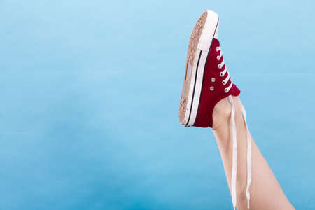 Footwear, fashion, shoes concept. Person tying laces in red sneaker with foot up, studio shot on blue background Stock Photo