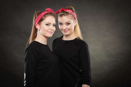 feel affection: Love and affection in family. Blonde gorgeous sisters stylized on retro pin up vintage style. Two girls in red handkerchief smiling feel enjoyable happy. Stock Photo