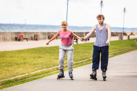Active jóvenes amigos en traje de entrenamiento patinaje al aire libre. La mujer y el hombre joven la mano disfrutando de una conducción deportiva. Foto de archivo
