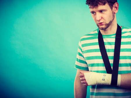 luxacion: Las fracturas y dislocaciones concepto. Hombre con la mano en el vendaje. medicamentos útiles para el brazo de palma dolorosa del individuo joven. Foto de archivo