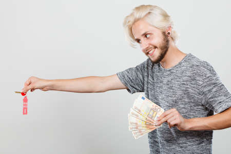Household savings and finances, economy concept. Happy man holding money and keys to house, studio shot on grey background