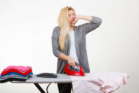 bored woman: Housewife problems, tiredness concept. Sleepy yawning bored woman standing behind ironing board, having lot of clothes to iron. Studio shot on white background Stock Photo