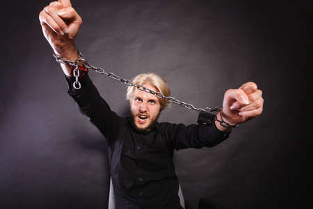 social problems: No freedom, social problems concept. Furious man with chained hands, studio shot on dark grunge background Stock Photo