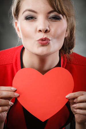 persuade: Love and help from people. Charming lovely woman with red paper heart persuade to be good helpful hopeful. Valentines Day or charity concept.