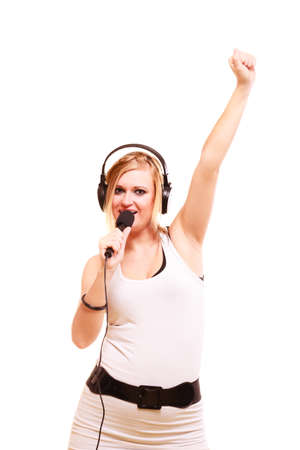Music, passion concept. Studio shot of blonde young woman singing to microphone and wearing big headphones on her head performing songs and having fun, isolated Stock Photo